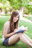 книга outdoors читая детенышей женщины Стоковая Фотография