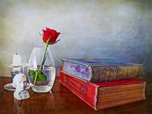 Книги антиквариатов, одиночная роза красного цвета и другое личное имущество Стоковое Фото
