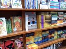 Книги аранжированные в полке на книжном магазине стоковые изображения