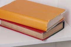 2 книги в крышке цвета на деревянных книжных полках задняя школа к Стоковые Фотографии RF