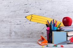 Книги и блокноты, канцелярские принадлежности и красное яблоко на деревянной предпосылке с изображением бумажного карандаша Стоковые Изображения RF