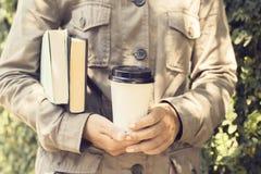 Книги и кофе нося девушки outdoors Стоковое Изображение