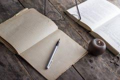 Книги и свечка на деревянной таблице Стоковые Фото