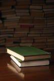 2 книги на деревянном столе против предпосылки несколько книг Стоковое фото RF
