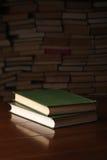 2 книги на деревянном столе против предпосылки несколько книг Стоковая Фотография