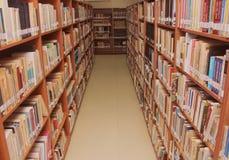 Книги на полке в библиотеке стоковые изображения