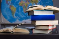 Книги на таблице с картой на предпосылке стоковые изображения
