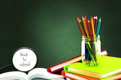 Книги, ручка, карандаш и лупа на зеленой доске, образовании и назад к вопросу школы, пути клиппирования стоковые изображения