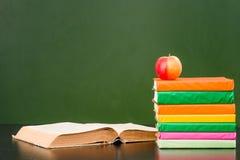 Книги с яблоком около пустой зеленой доски образец для текста Стоковое Фото