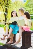 Книги чтения детей на парке Девушки сидя против деревьев и озеро внешнее Стоковая Фотография RF
