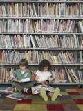 Книги чтения мальчика и девушки в библиотеке Стоковое Изображение RF