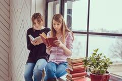 2 книги чтения молодых студента женских сидя на силле окна Стоковое фото RF