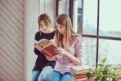 2 книги чтения молодых студента женских сидя на силле окна Стоковые Изображения