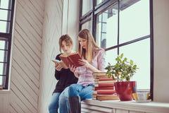 2 книги чтения молодых студента женских сидя на силле окна Стоковая Фотография RF