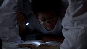Книги чтения ребенка на ноче под одеялом, освещении себя с электрофонарем стоковые фотографии rf