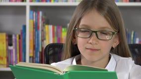 Книги чтения ребенка студента в библиотеке, девушке школы изучая учить на столе 4K сток-видео