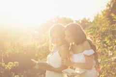 2 книги чтения сестер Заход солнца Стоковые Фотографии RF