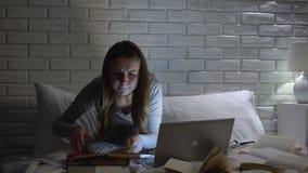 Книги чтения студентки, печатая проект на ноутбуке поздно вечером, крайний срок акции видеоматериалы