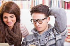 Книги чтения человека и женщины совместно дома стоковые фото