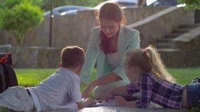 Книги чтения outdoors, веселый женский гувернер прочитали книгу для мальчика и девушки сидя на зеленой траве на под открытым небо видеоматериал