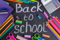 Книги школьных принадлежностей, случай карандаша, карандаши в стекле и тетрадь на предпосылке школьного правления с надписью стоковые изображения rf
