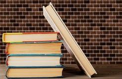 Книги штабелированные вертикально и одна книга близко стоковое фото