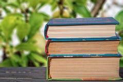 Книги штабелированные вертикально на конце стола вверх стоковое изображение