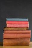 Книги штабелированные на столе класса с предпосылкой доски стоковое изображение