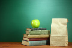 Книги, Яблоко и обед на столе учителя стоковые изображения