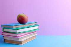 Книги y красочные и яблоко на яркой пестротканой голубой и розовой предпосылке близкие поставкы школы транспортира компаса вверх стоковое фото