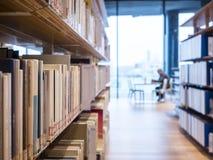 Книжная полка библиотеки с образованием людей читая внутренним стоковые фото