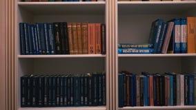 Книжные полки в домашней библиотеке Много книги на полке акции видеоматериалы