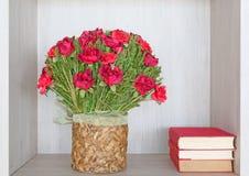 Книжные полки с стогом античных книг и цветков в библиотеке Стоковые Изображения RF