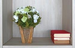 Книжные полки с стогом античных книг и цветков в библиотеке Стоковое Фото