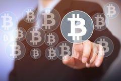 Кнопка Bitcoin на виртуальном интерфейсе показывая, бизнесмене касаясь символу валюты стоковое изображение