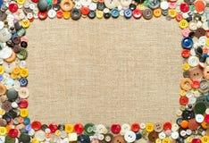 Кнопки обрамляют на предпосылке ткани Стоковая Фотография RF