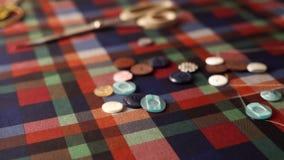 Кнопки одежд красочные падают на ткань шотландки в замедленном движении Кнопки белошвейки бросая на ткани в slomo в портное сток-видео