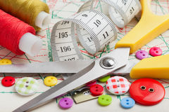Кнопки, цветастые ткани, ножницы, измеряя лента, катышкы резьбы Стоковое фото RF
