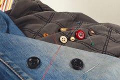 Кнопки, штыри и иглы с потоками на предпосылке одежд черного хлопка и голубых джинсов закрывают вверх Стоковое фото RF