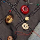 Кнопки, штыри и иглы с потоками на черных хлопке и крупном плане одежд голубых джинсов Стоковая Фотография