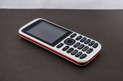 Кнопочный мобильный телефон на серой предпосылке стоковая фотография