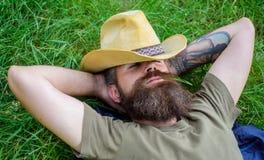 Ковбой человека бородатый кладет на траву ослабляя или имея ворсину Ковбой ослабляя на зеленом луге Зверский ковбой с зеленым цве стоковые фотографии rf