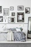 Ковер перед кроватью и зеркало в белом и черном интерьере спальни с галереей Реальное фото стоковое фото rf
