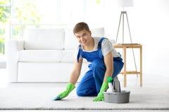 Ковер человека очищая белый в живущей комнате стоковая фотография