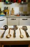 Ковши на деревянном столе на предпосылке кухни Стоковые Изображения