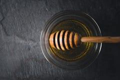 Ковш меда в опарнике с медом на темном каменном взгляде столешницы Стоковые Изображения RF
