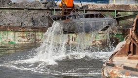 Ковш экскаватора выкапывая в песке от воды Стоковое Изображение RF