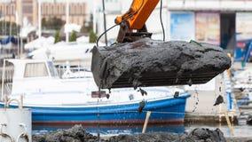 Ковш экскаватора выкапывая в песке от воды Стоковые Фото