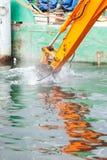 Ковш экскаватора выкапывая в песке от воды Стоковое фото RF