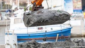 Ковш экскаватора выкапывая в песке от воды Стоковые Изображения RF